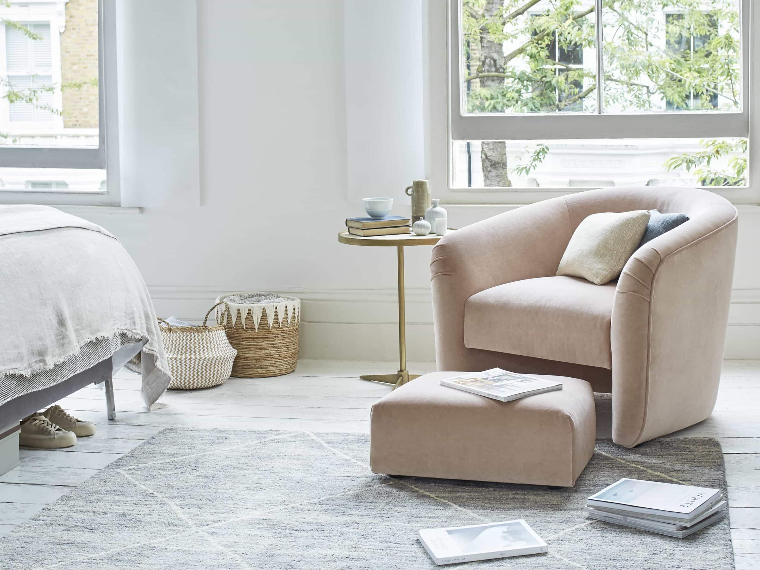 blush pink armchair with matching ottoman in bedroom corner white floors