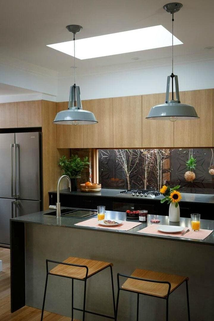 charcoal grey kitchen with light timber cabinets and industrial grey metal pendants over kitchen island