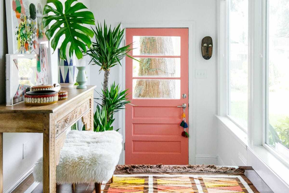 colourful entryway with coloured aztec rug pink door and moroccan side table