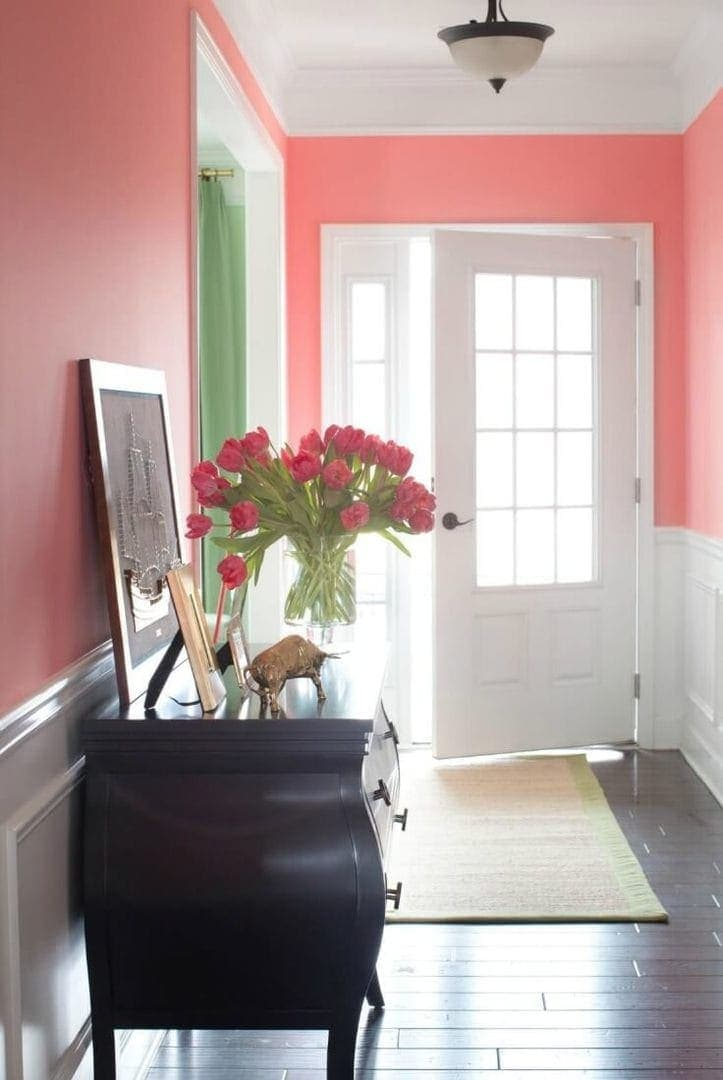 entryway with pink walls and white timber cladding and dark brown stained floorboards - hallway design