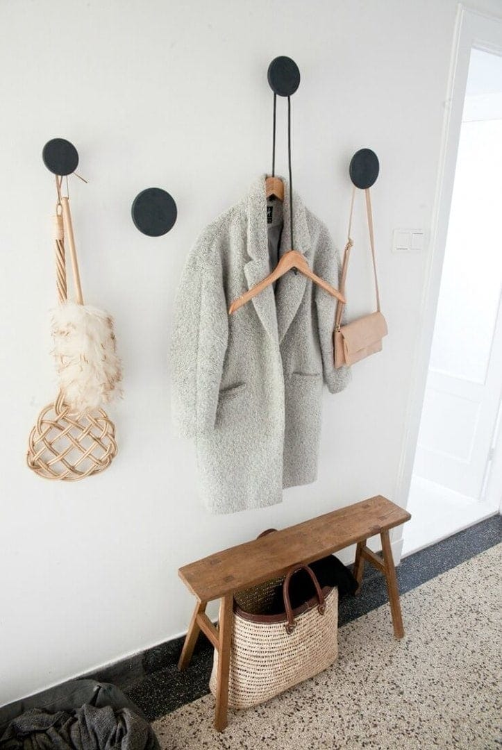 grey coat on stylish black round wall hook in entryway with small timber bench stool - hallway design