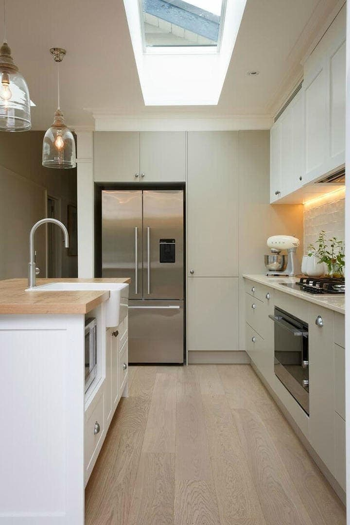 light olive green kitchen cpboards with shaker style door handles and light timber floor