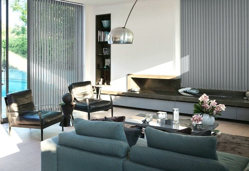 grey vertical blinds from luxaflex in living room with black leather armchairs