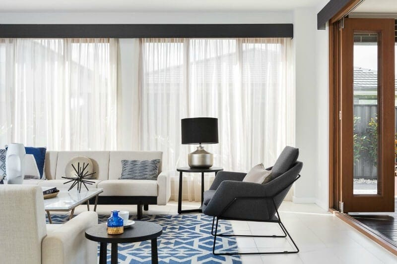 sheer curtains in living room with blue and white aztec rug and cream sofa