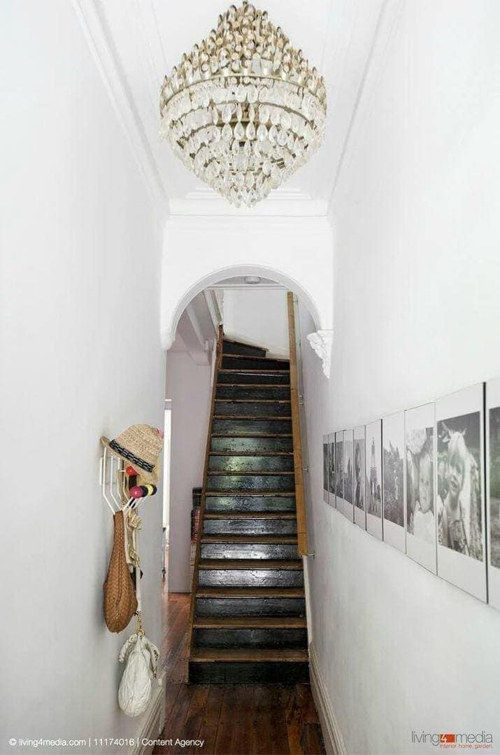 terrace house hallway with vintage chandelier light and black staircase - hallway design