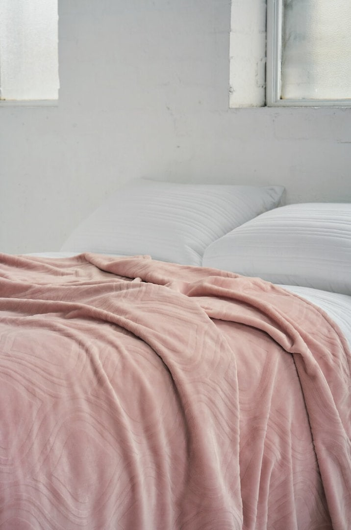 textured pink blanket on white bed with exposed brick wall from lorraine lea bedding