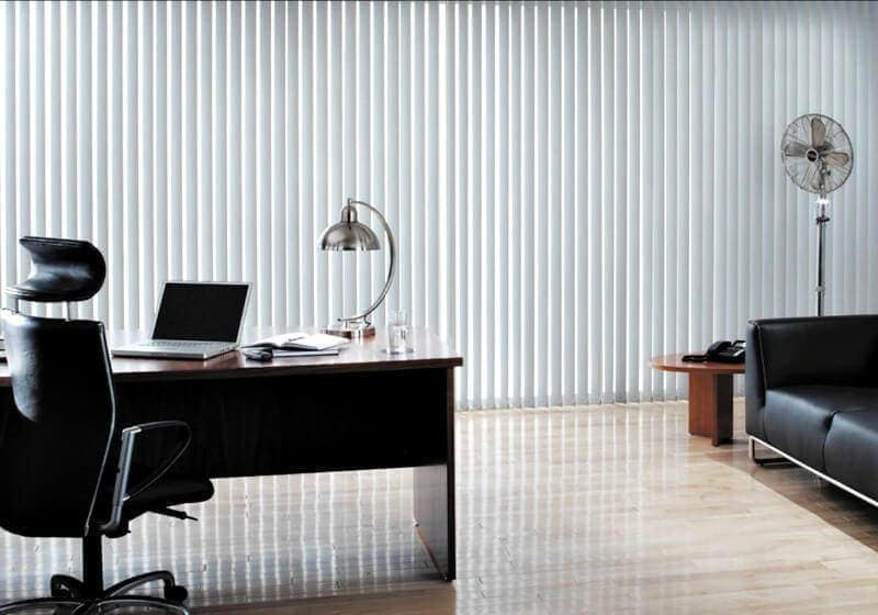 vertical blinds in an office with polished floorboards and black leather sofa