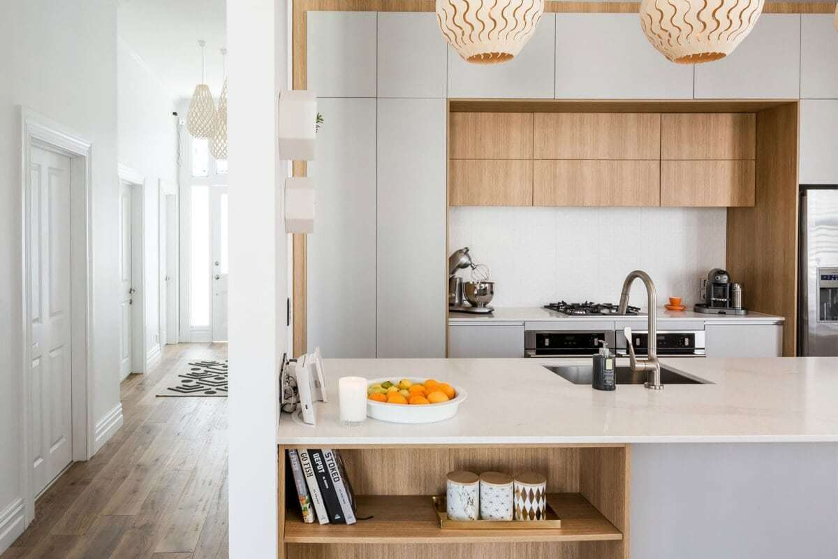 white and blonde timber kitchen with round timber pendant lights over benchtop