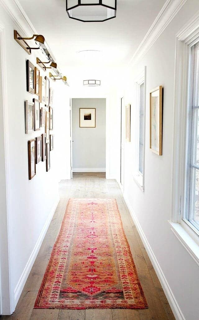 white hallway with red moroccan rug and vintage frame gallery wall