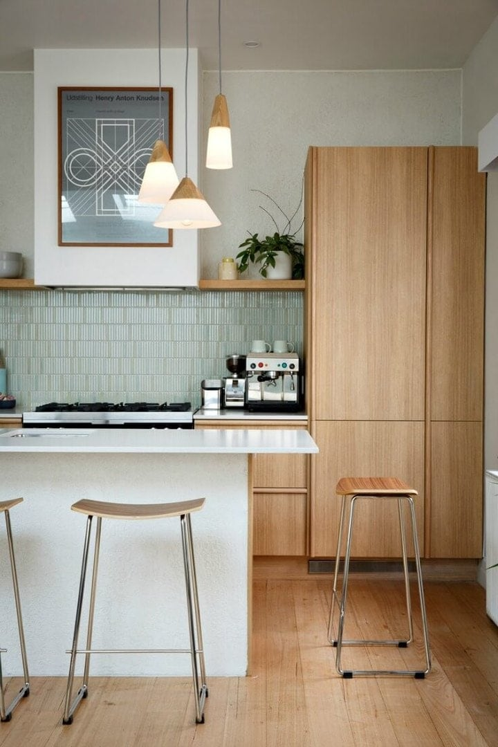 white kitchen with light blond timber cabinets and olive green splashback tiles reno rumble