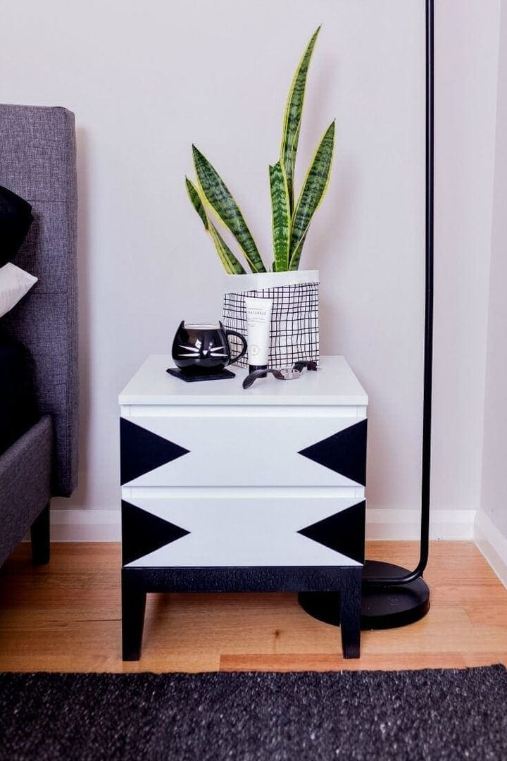 black and white aldi bedside table hack with black cat mug and mother in laws tongue plant