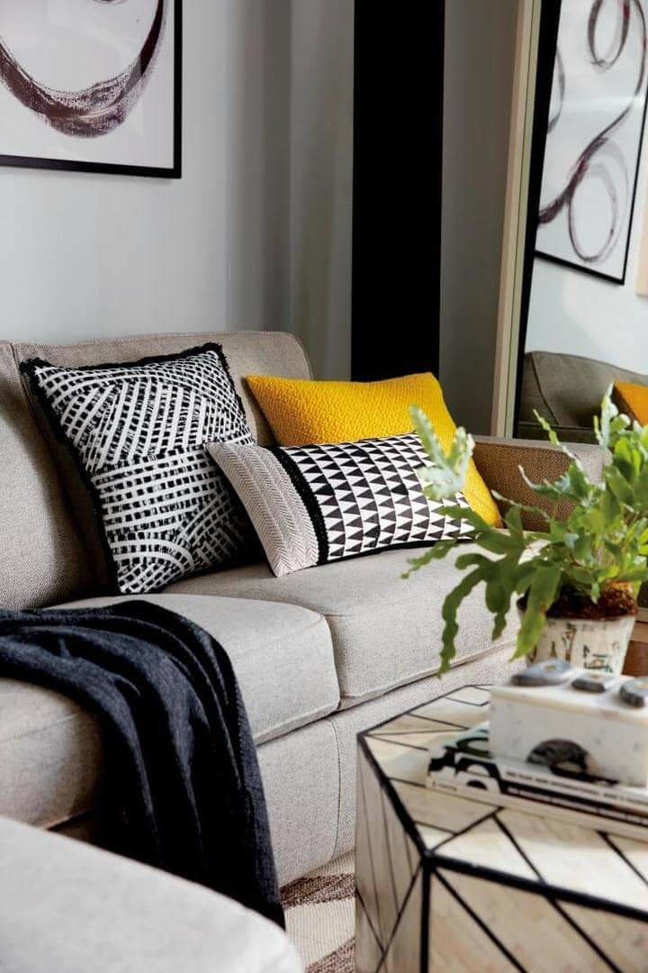 black white and yellow cushions on grey sofa with tribal patterns from west elm