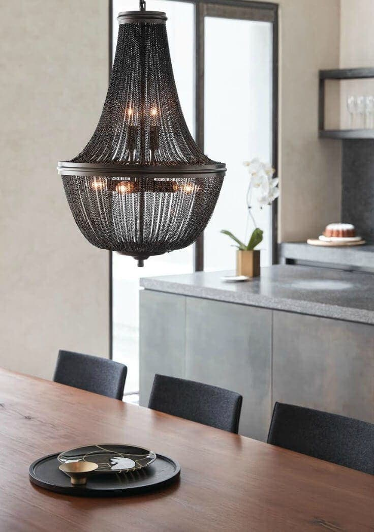 black wire mesh pendant light from beacon lighting above timber dining table and black felt chairs