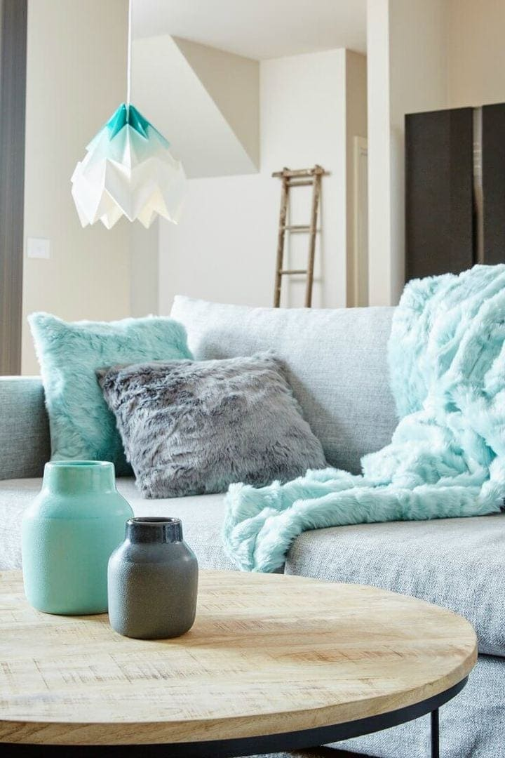 mint and grey faux fur cushions on grey sofa with mint and white paper pendant light