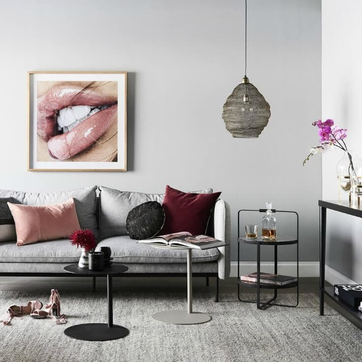 nathan and jac grey and maroon living room with blush cushions and black furniture