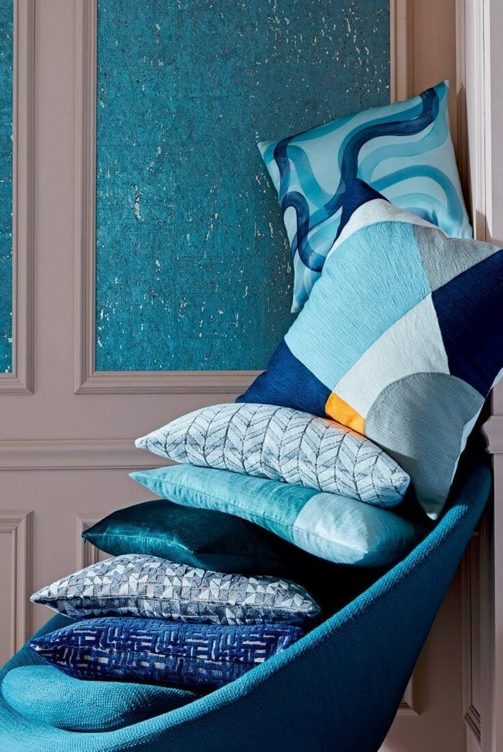 stack of blue and white cushions on blue armchair from west elm