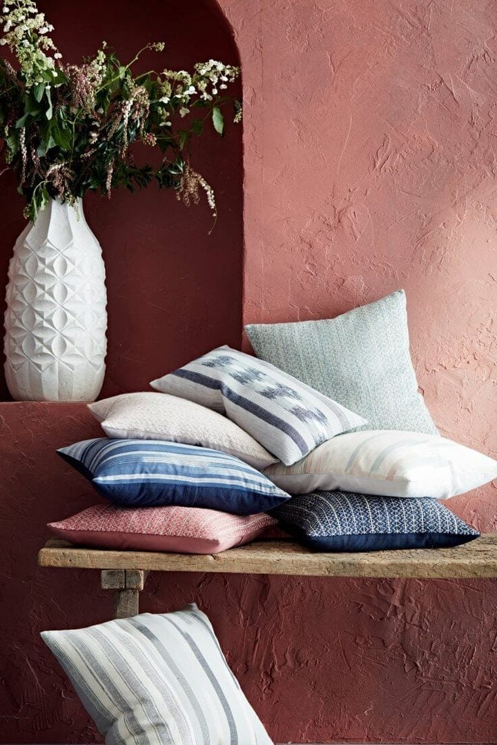 stack of cushions on rustic timber bench against terracotta feature wall from west elm