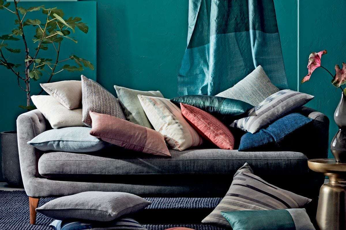 stack of cushions on grey sofa from west elm against teal blue feature wall