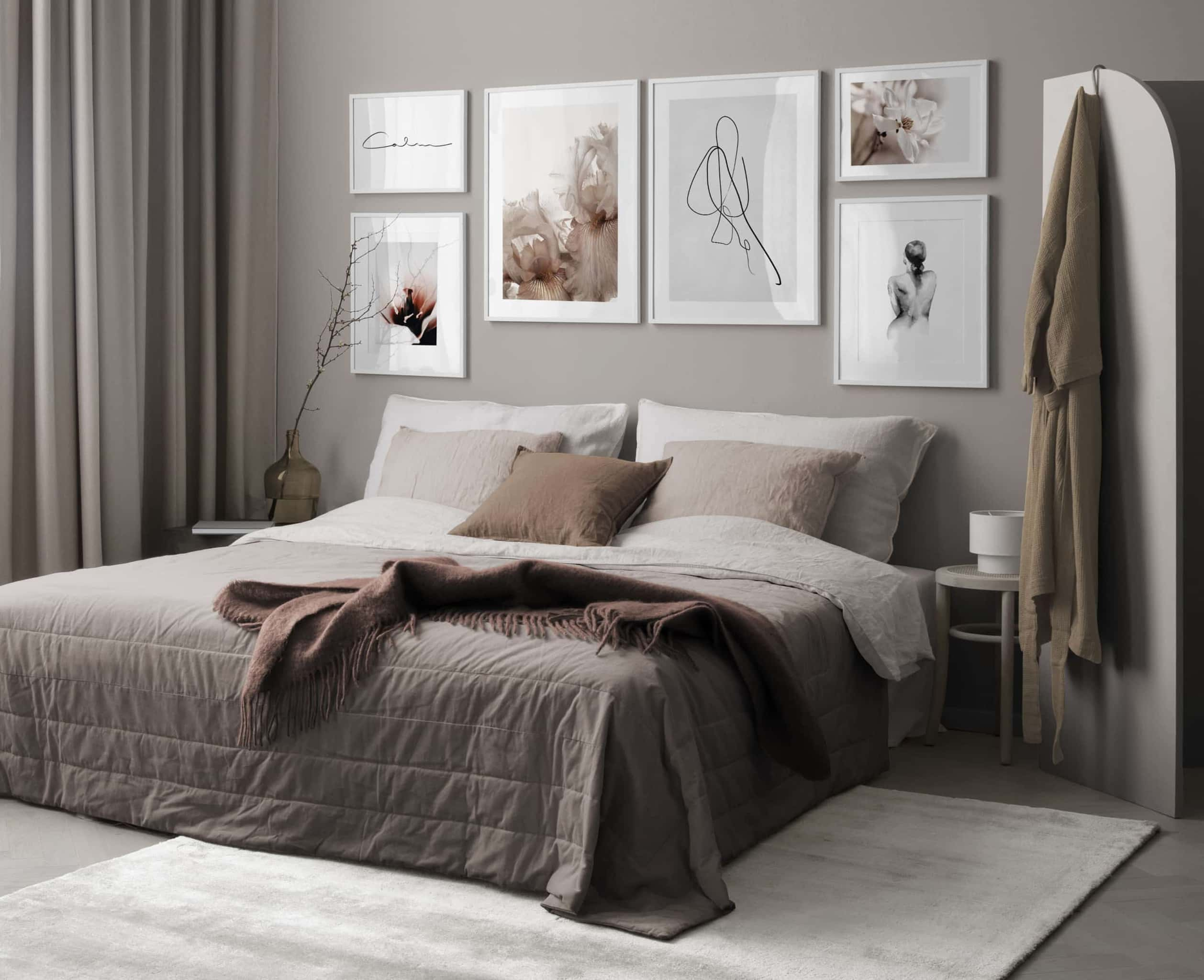 gallery wall of frames above bed in moody brown bedroom desenio