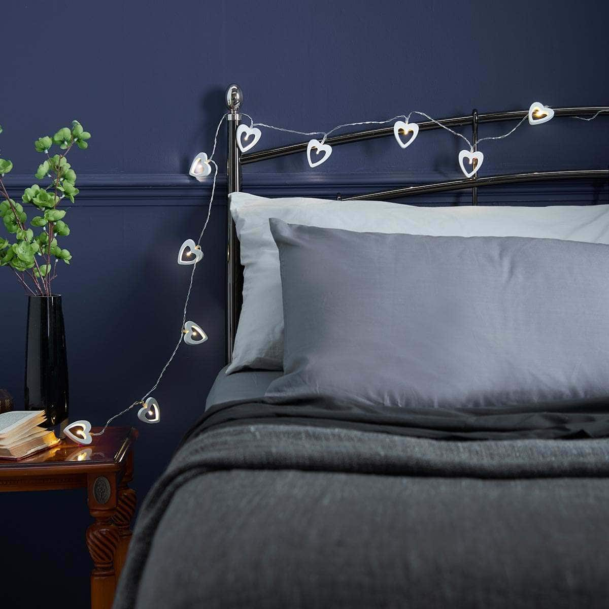heart shaped fairy lights above black frame bed