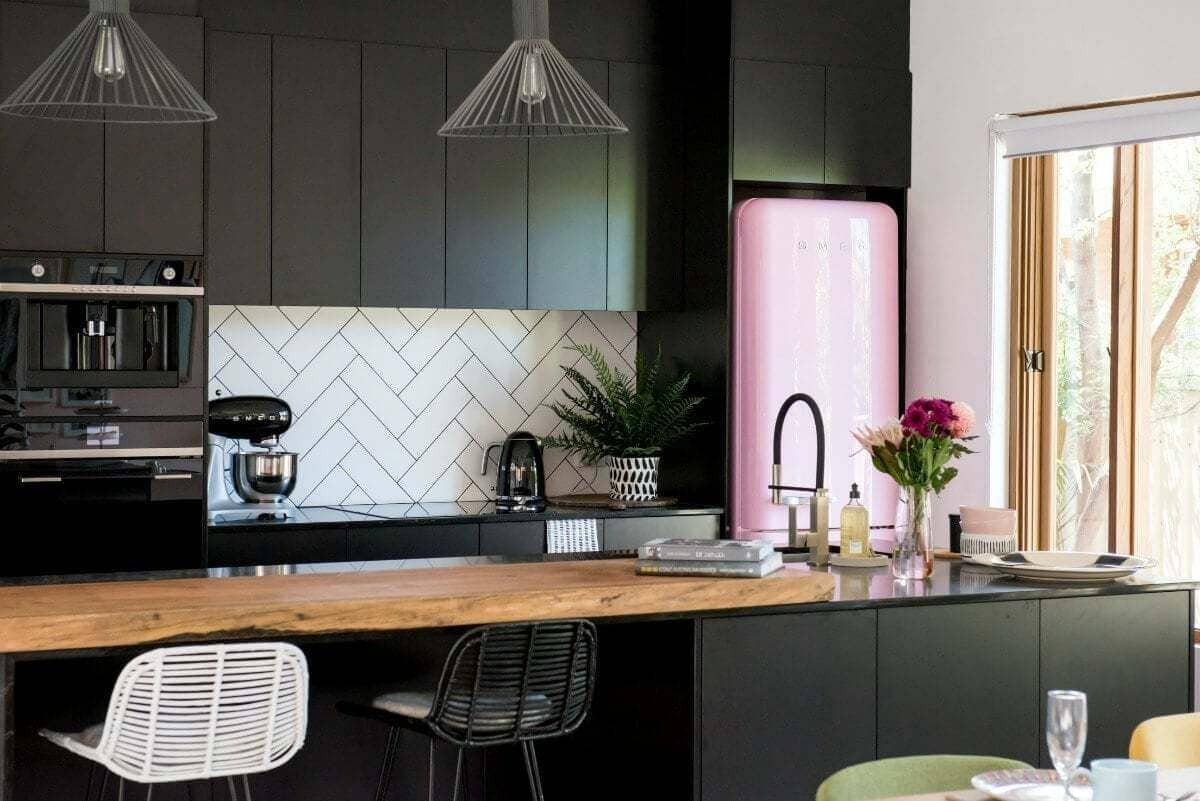 house rules 2017 black kitchen with white subway tile splashback and pink smeg fridge