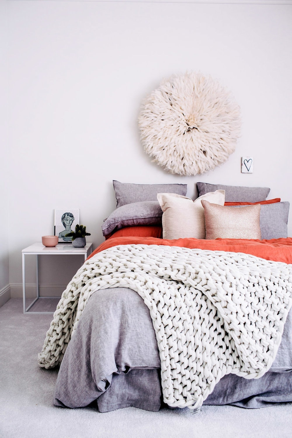 juju hat above bed with grey bedding and orange sheet set