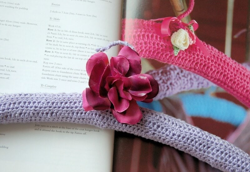 knitted coat hanger cover in purple and pink