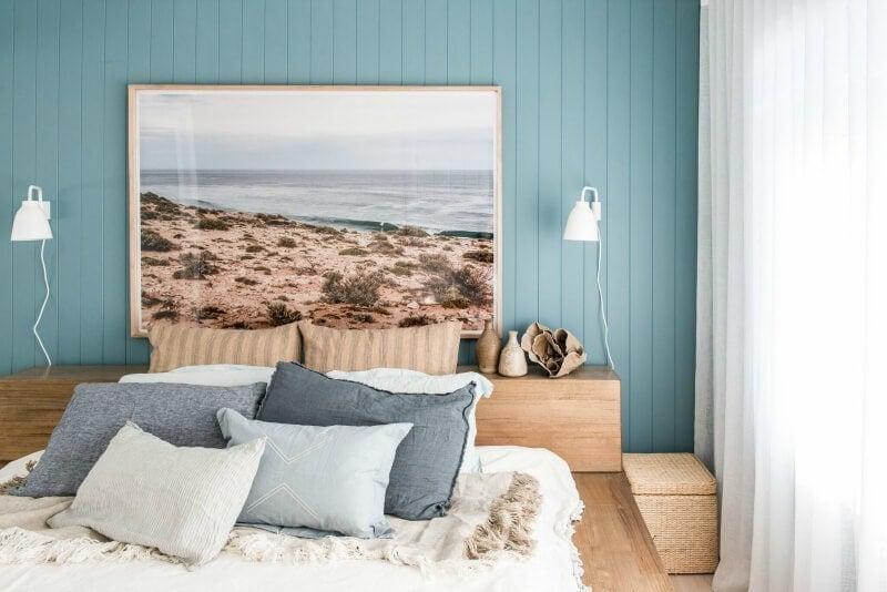 kyal and kara renovation bedroom with teal timber panelling and coastal wall art