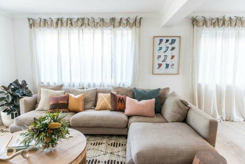 kyal and kara renovation living room with sheer curtains and beige sofa