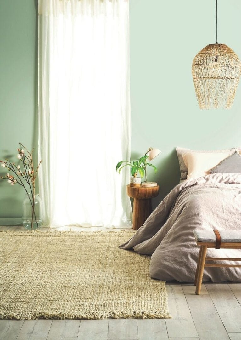 light green bedroom walls with taupe bed linen and sheer curtaisns from taubmans paint