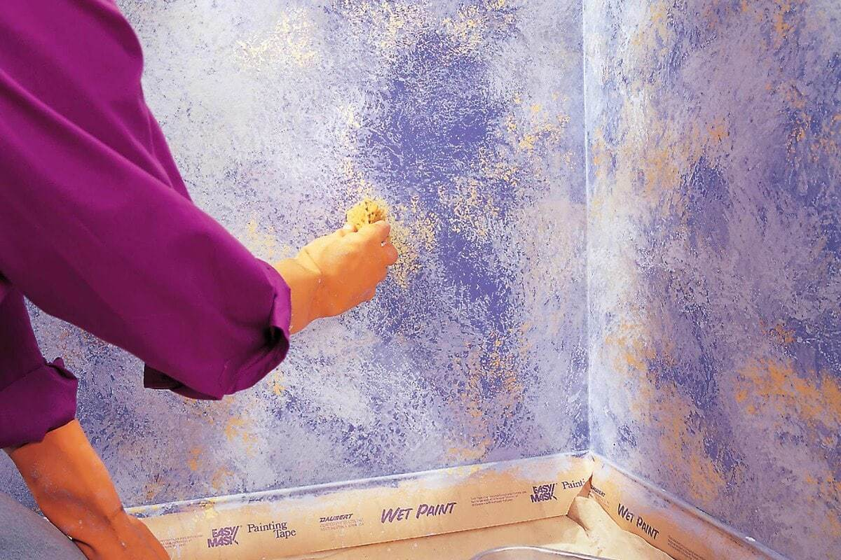 paint sponging a wall with purple paint