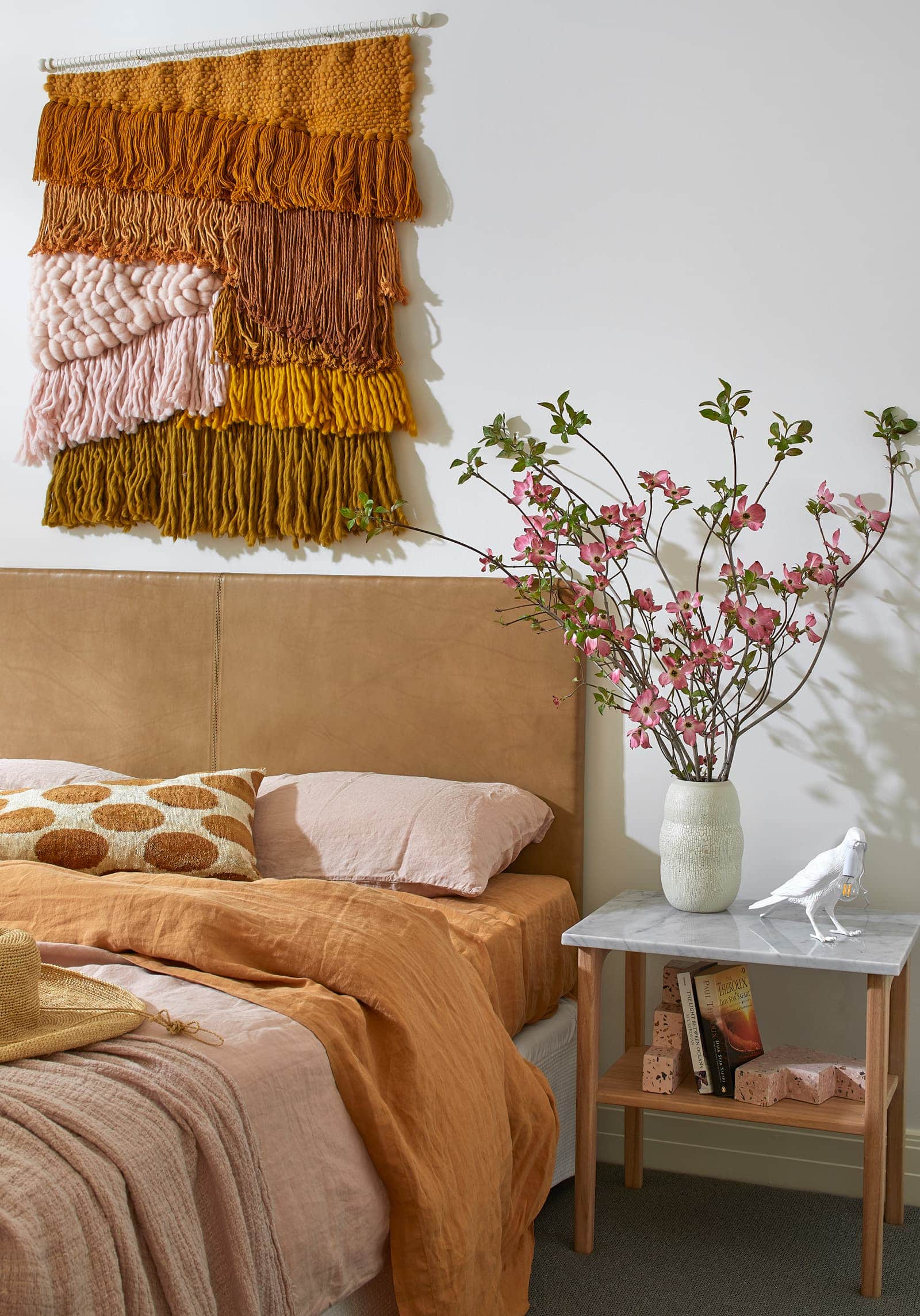 red-and-orange-textural-wall-hanging-above-headboard-in-bedroom
