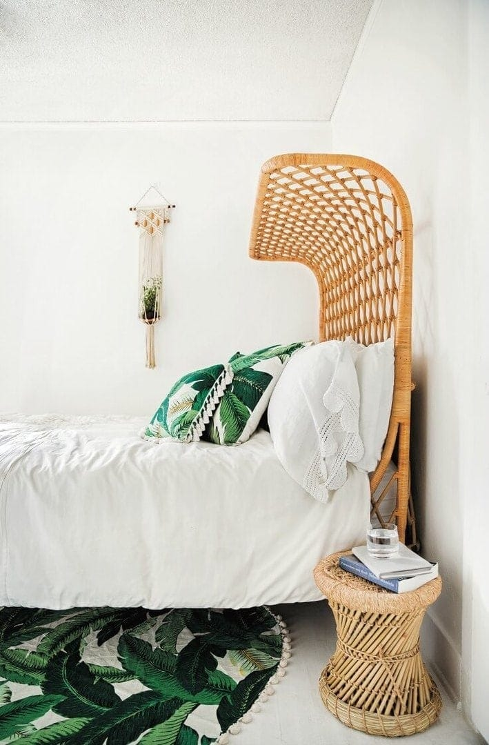 tropical bedroom with leaf pattern rug and curved rattan bedhead