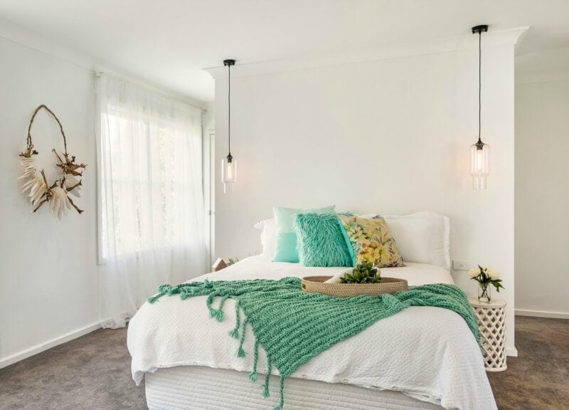 white bedroom with coastal style tropical green bedding and cushions
