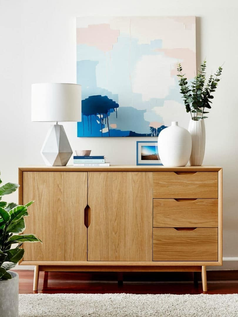 blonde timber sideboard styling with abstract artwork and concrete lamp