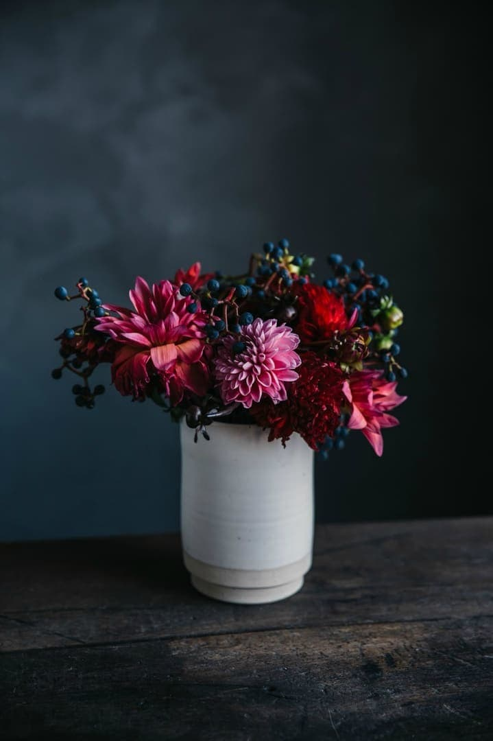 white vase of flowers with pink and red flowers against smokey charcoal feature wall