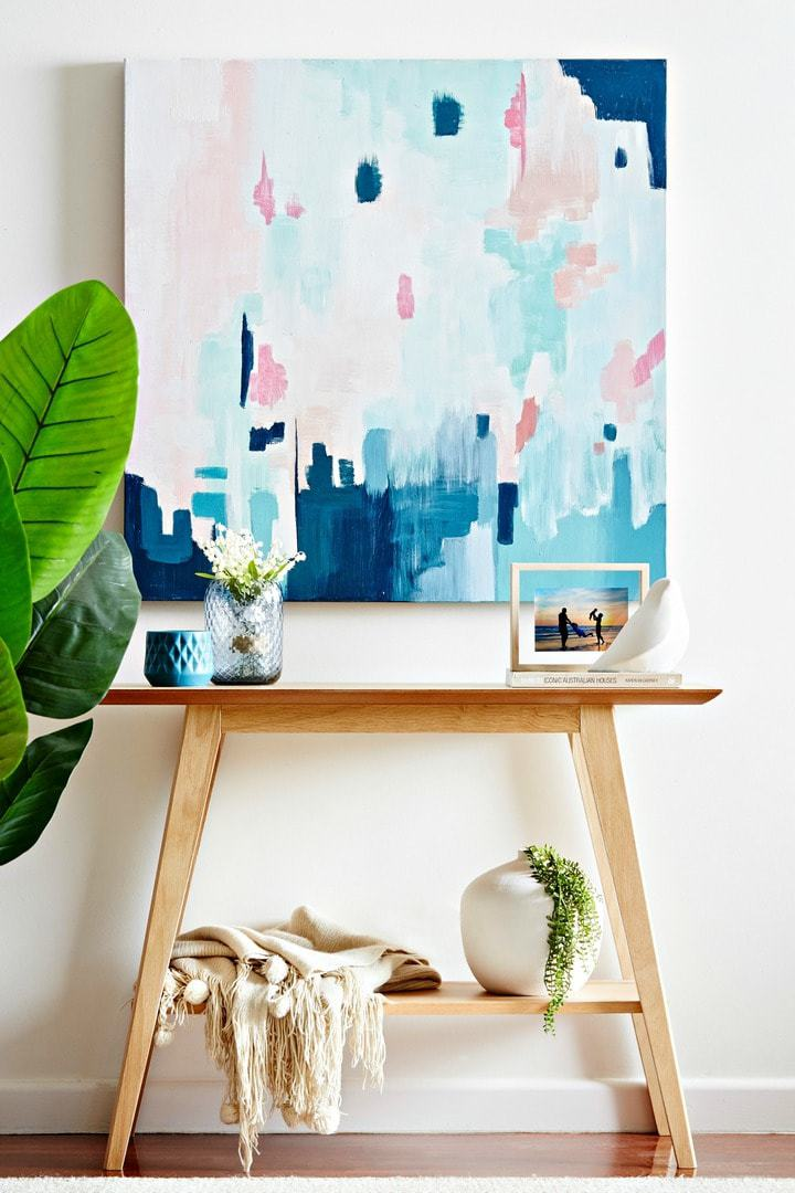 blonde timber console table with bright pink and blue artwork and artificial plant by tlc interiors