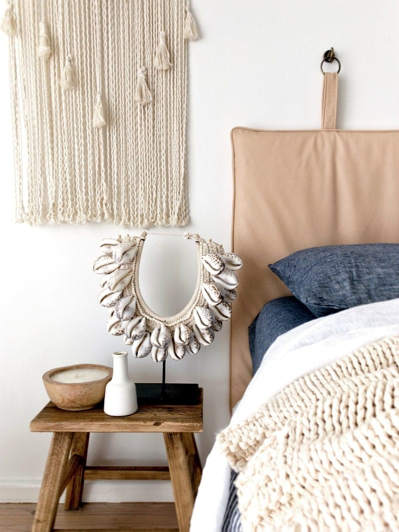 tan leather headboard in bohemiam bedroom with macrame wall hanging