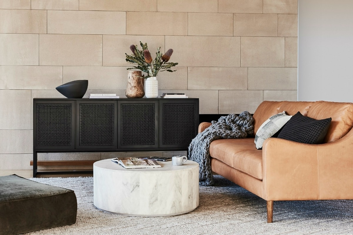 tan leather sofa in living room with round marble coffee table