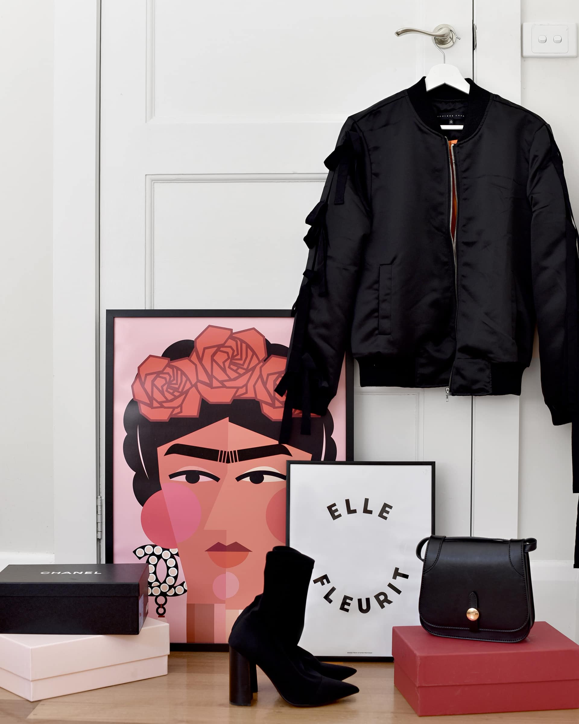 Frida artwork leaning against white wall with leather jacket