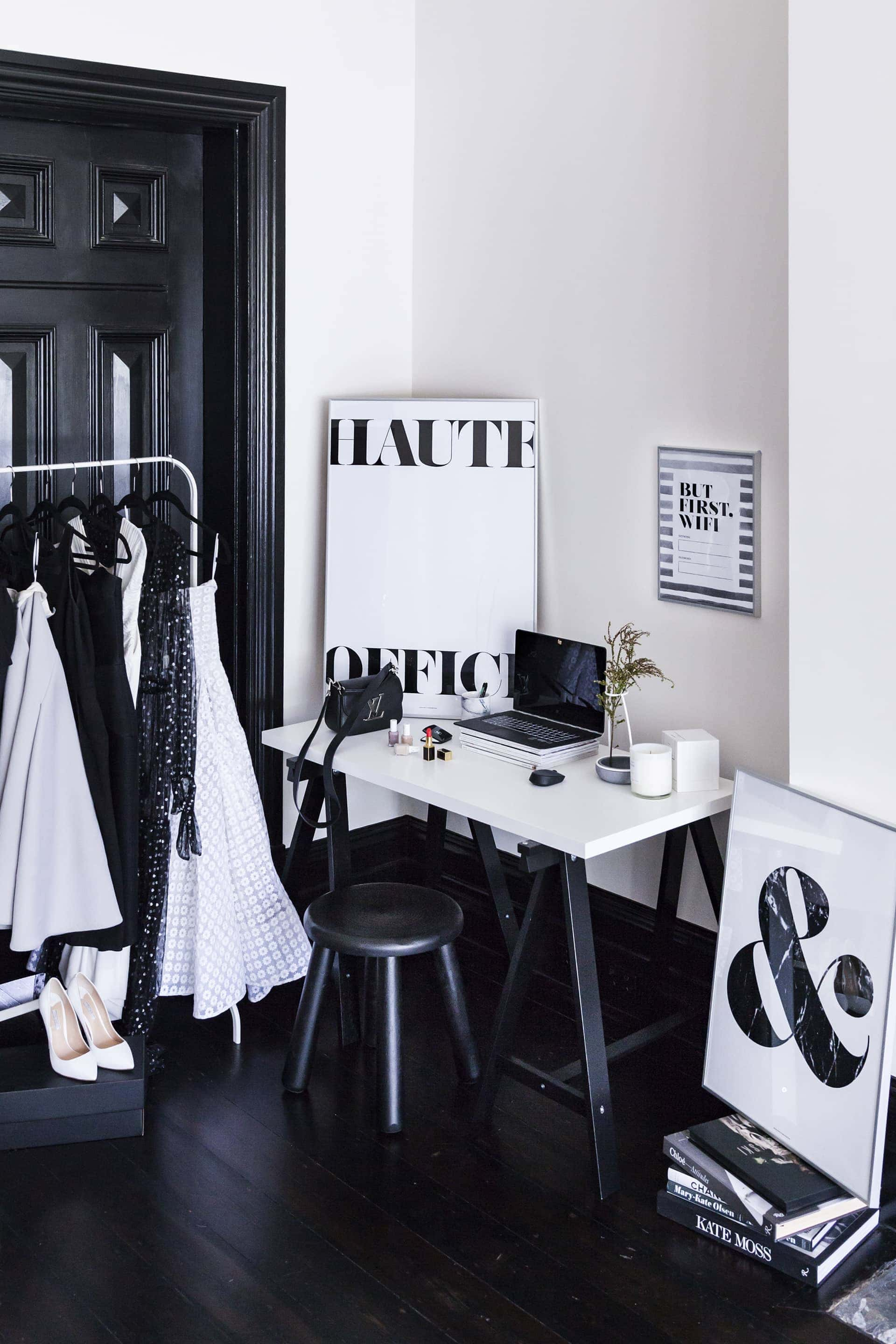 black and white fashion inspired home office with white testle table and clothing rack