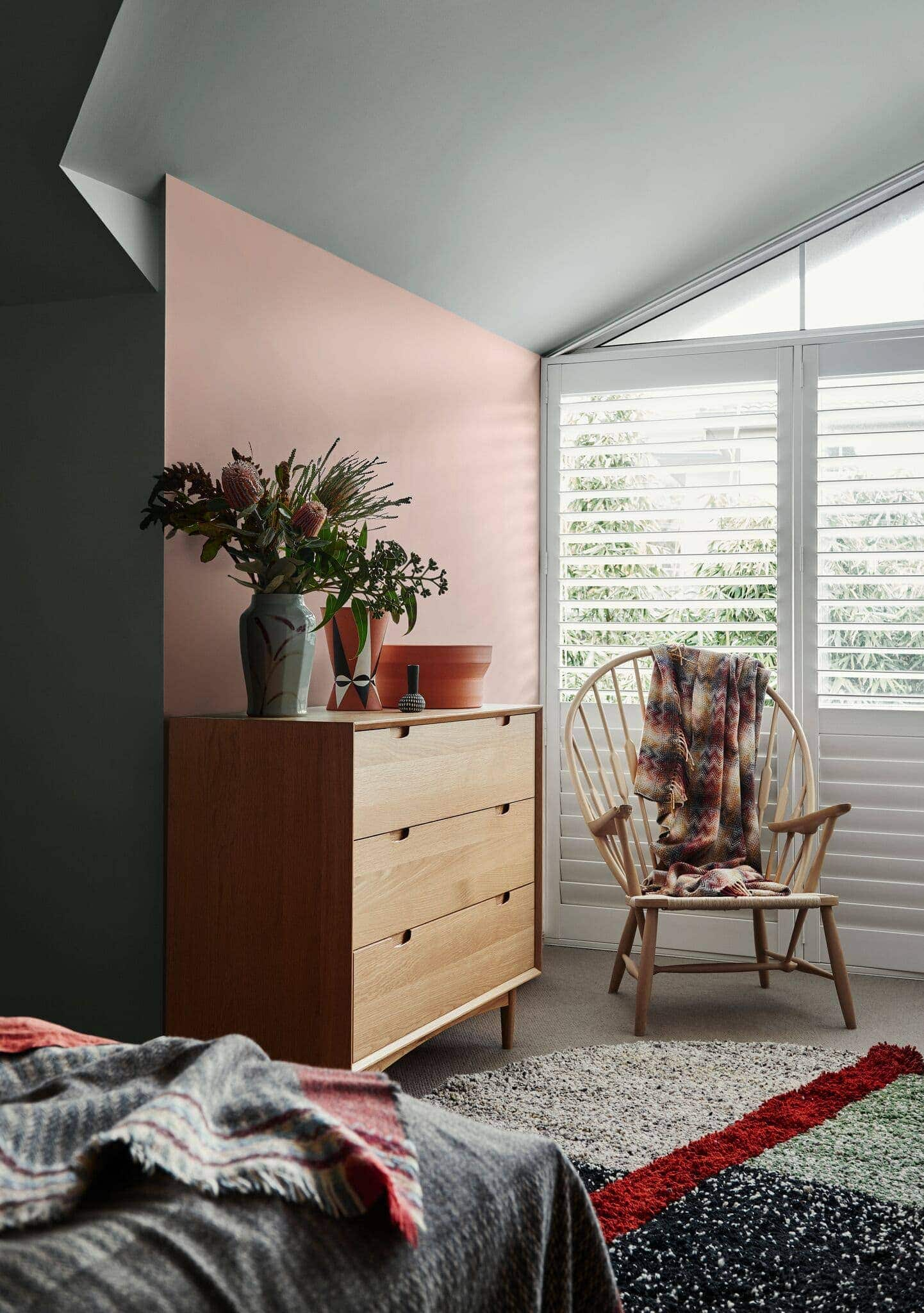 blush and green bedroom wall with blonde timber tallboy and timber rocking chair