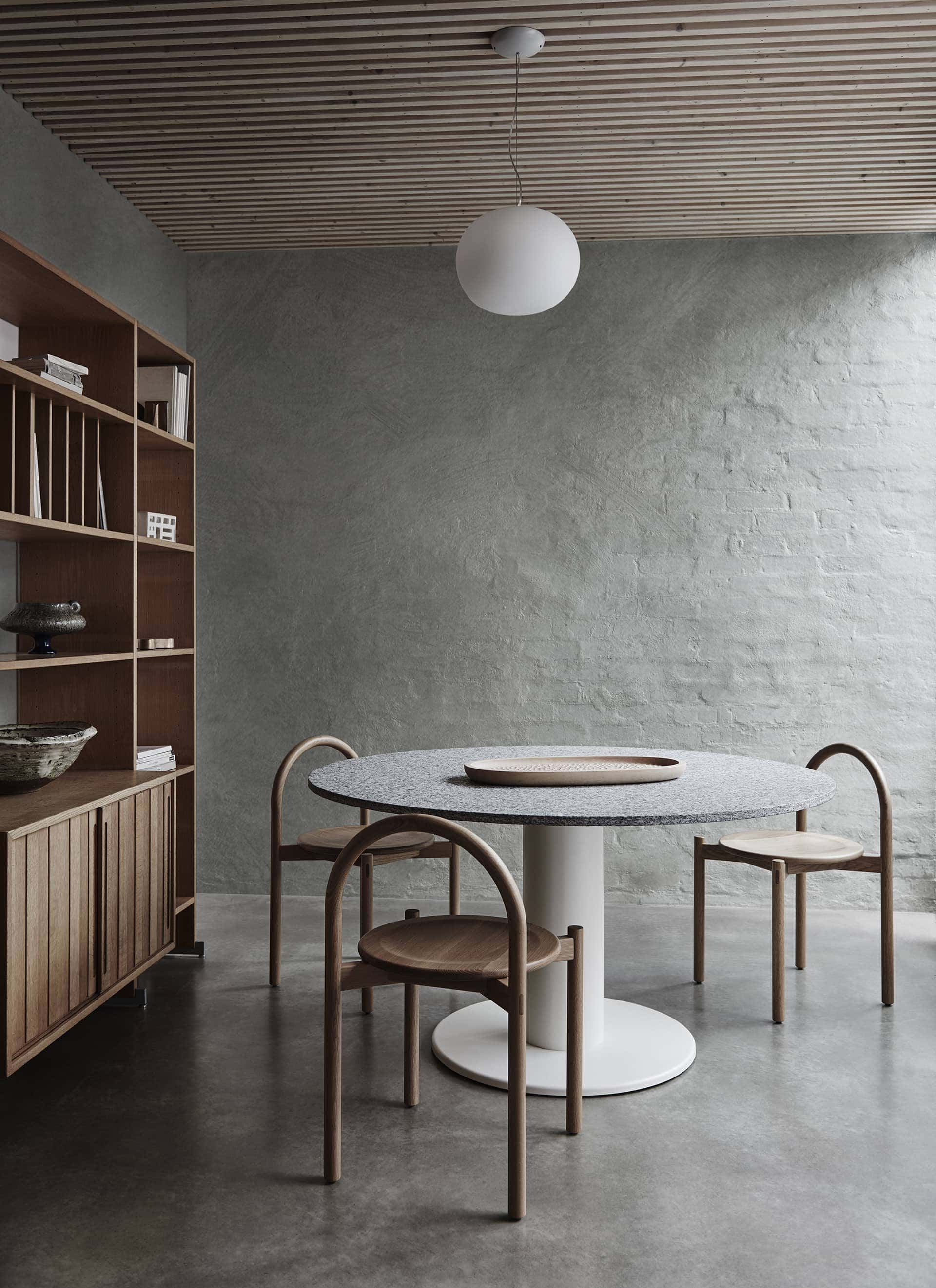 dining room with polished concrete floor and rendered brick wall