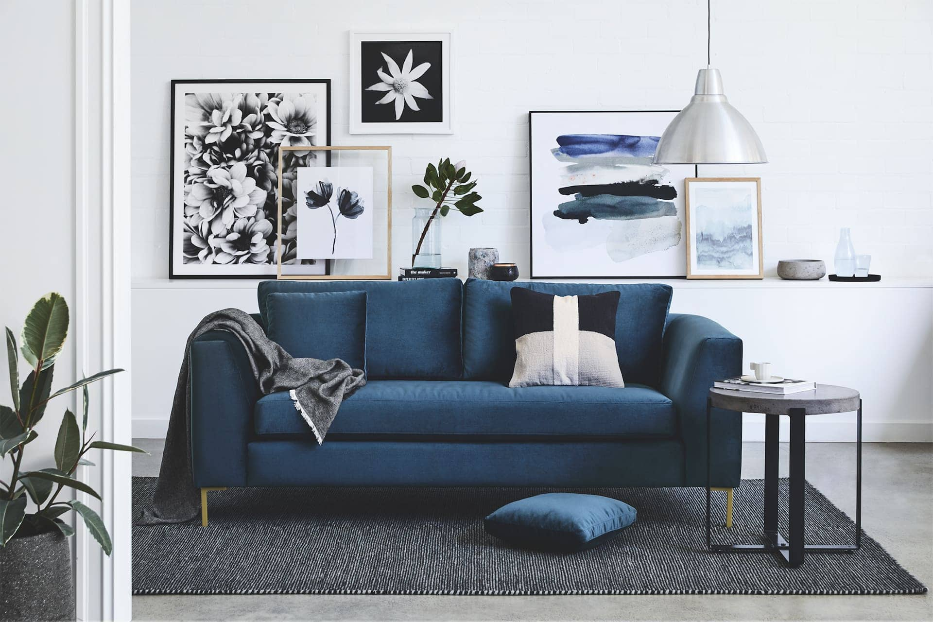 floral art gallery wall in living room with blue sofa from sheridan