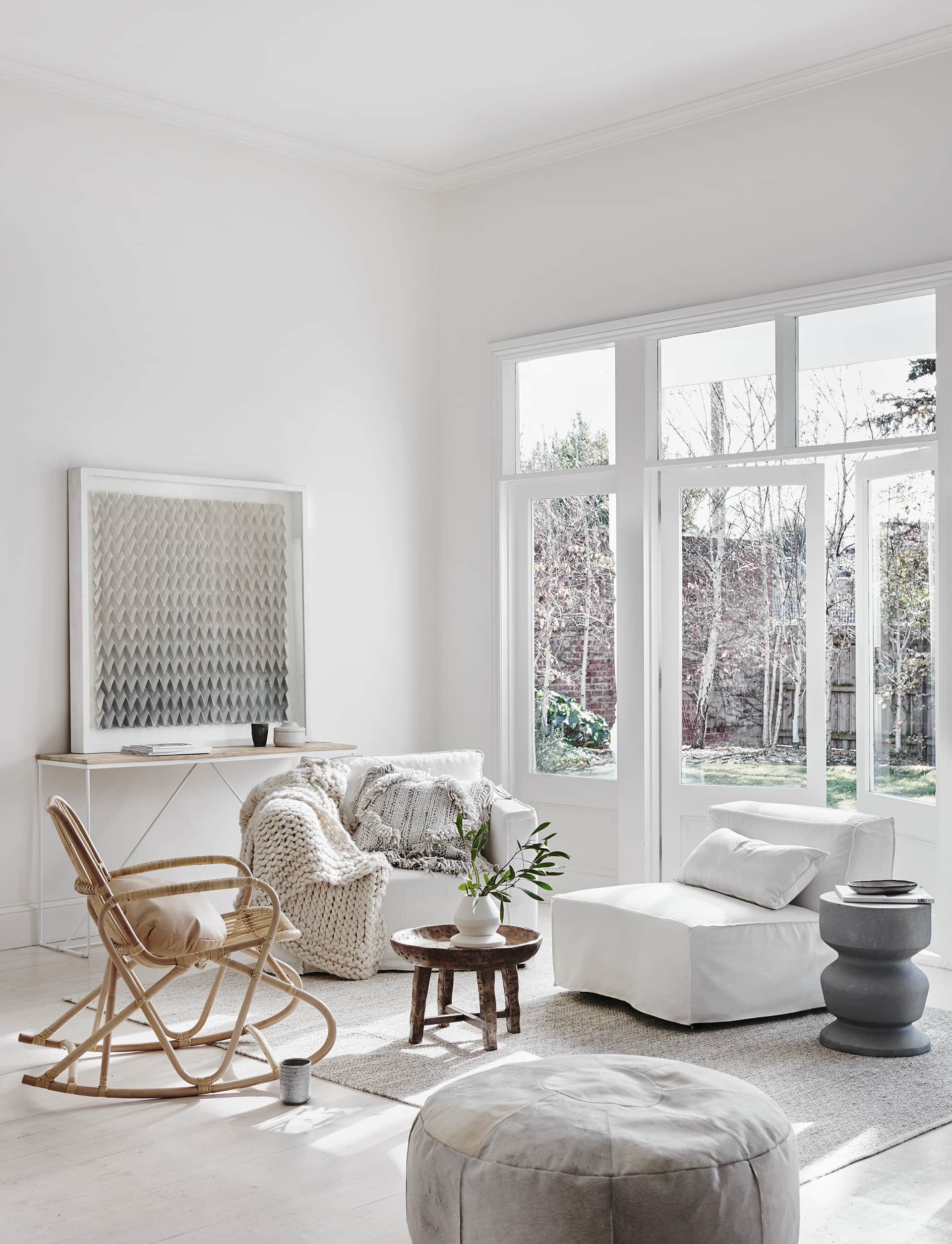 globewest white living room with white slip cover armchairs and rattan rocking chair