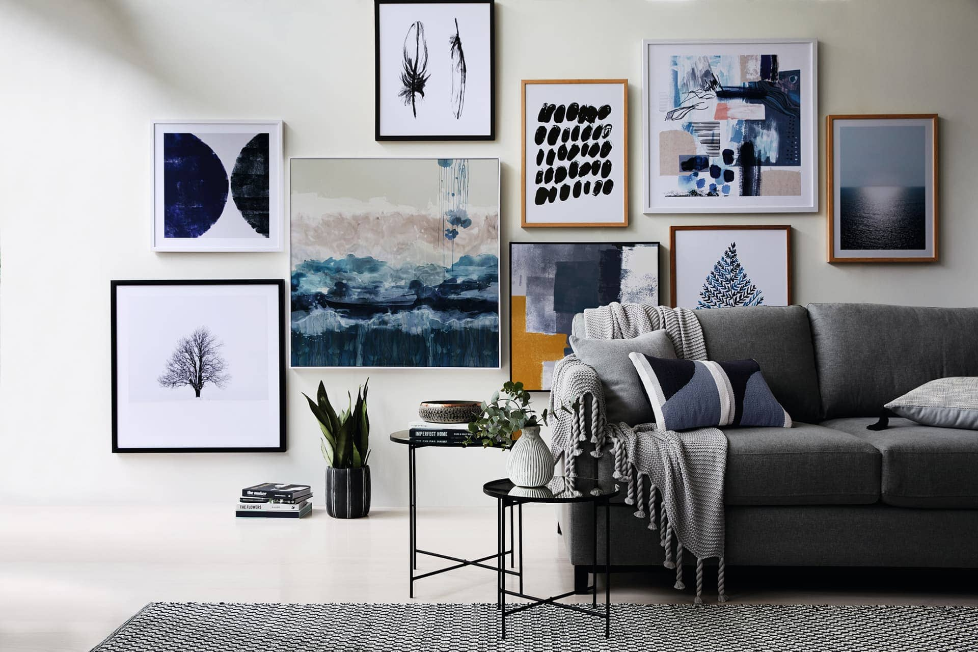 living room gallery wall with dark bllue and grey art from sheridan