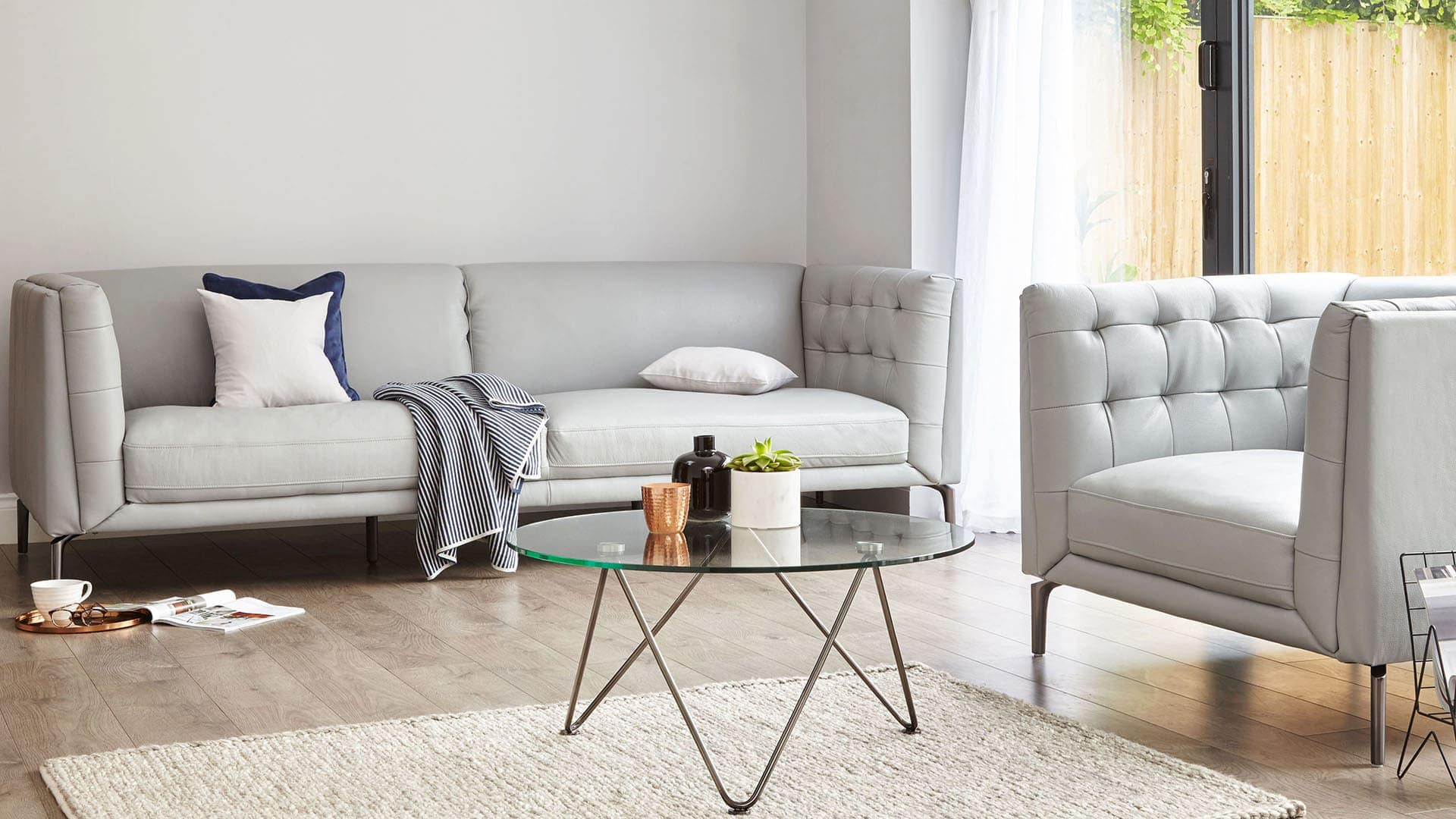 soft grey sofas in living room with round glass coffee table