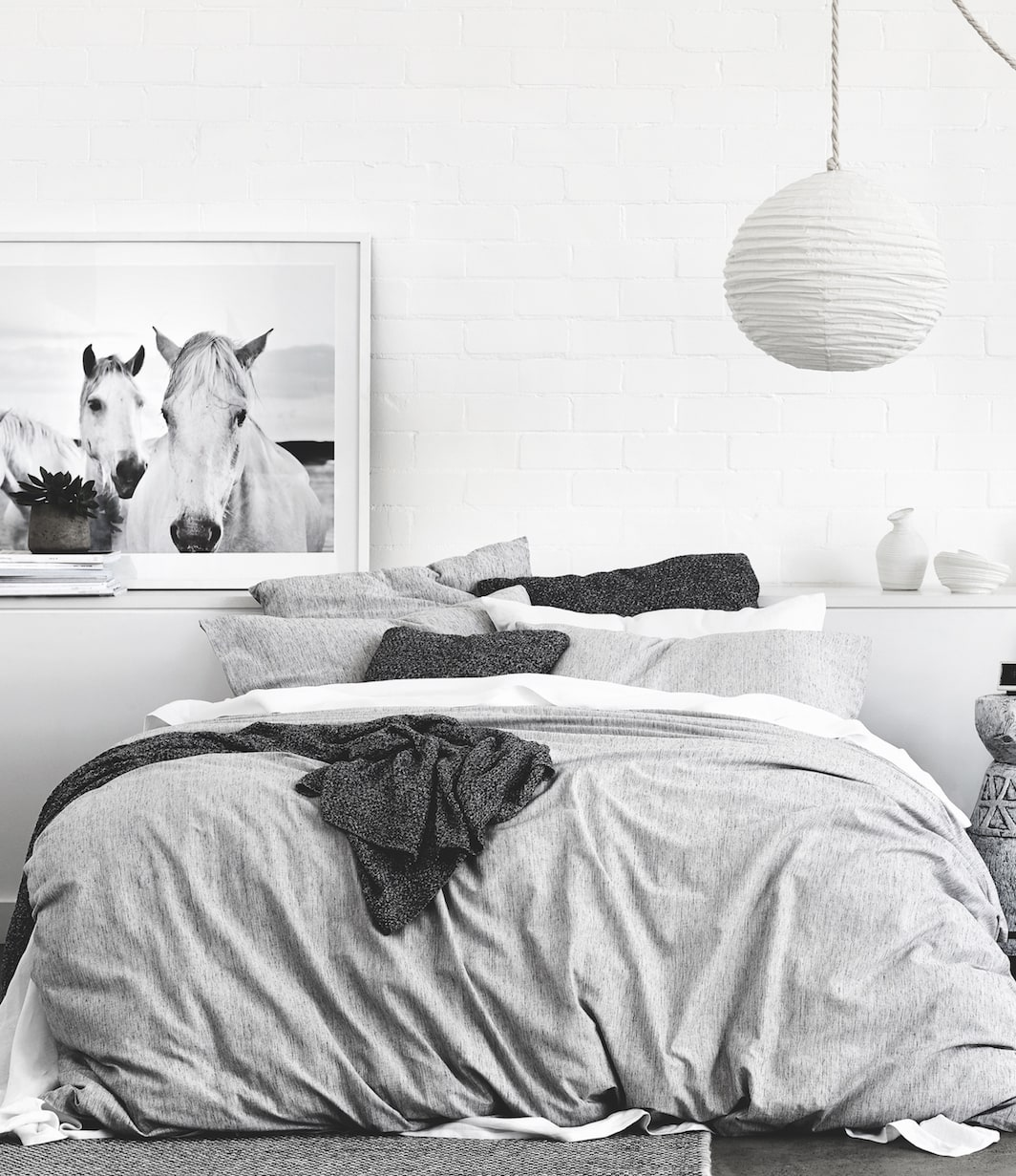 white bedroom with grey bedding and white horse art by sheridan