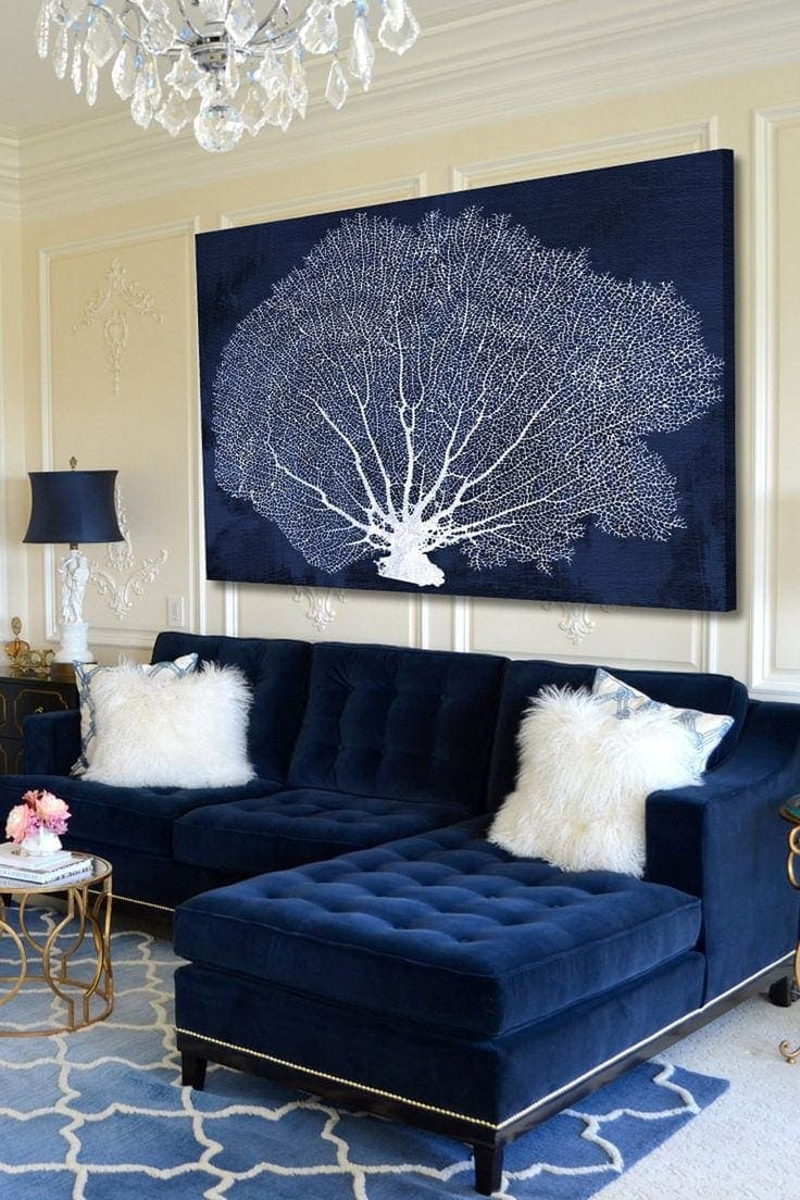 tufted blue velvet sofa with white faux fur cushions in living room