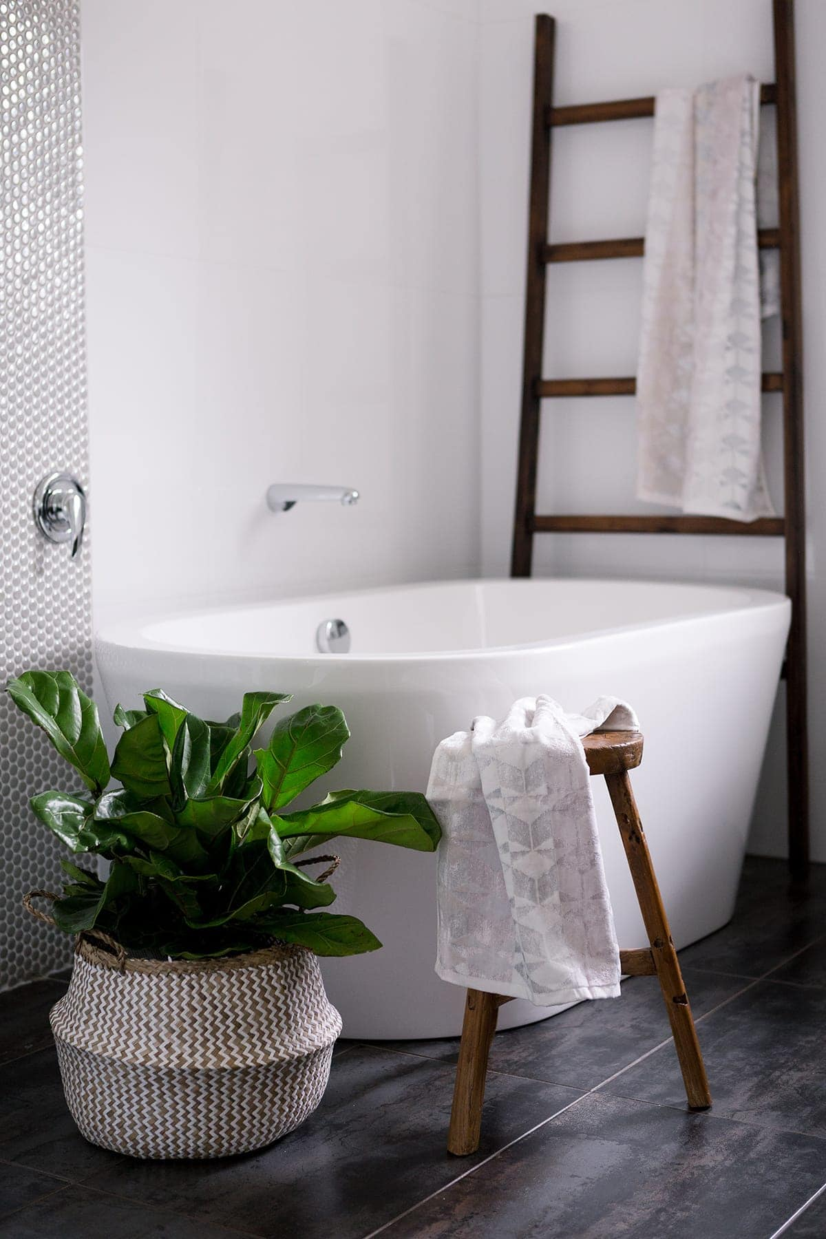 bathroom with freestanding bath and rustic ladder with fiddle lead fig in belly basket
